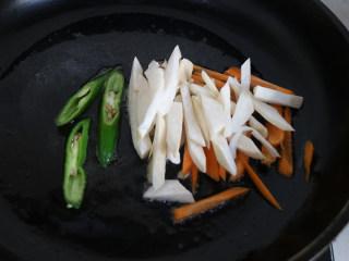 快手正餐 三丝杏鲍菇,再另起锅放入适量油,热油锅,放入少许蒜头、生姜,放入杏鲍菇胡萝卜丝辣椒丝,进行翻炒。