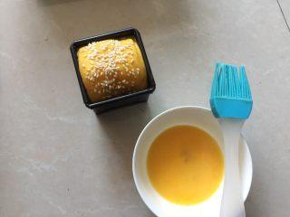 南瓜沙拉肉松小吐司 ,取出发酵好的吐司,在表面上刷上薄薄的蛋黄液,撒上白芝麻
