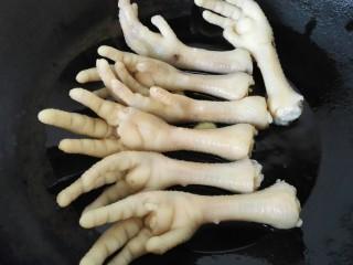 五香鸡爪,锅内放油烧热,加入适量蒜头煸炒香放入鸡爪