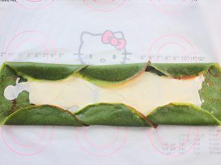 那一抹毛巾卷的绿,将饼边依次向内折叠,这样可以避免奶油漏出