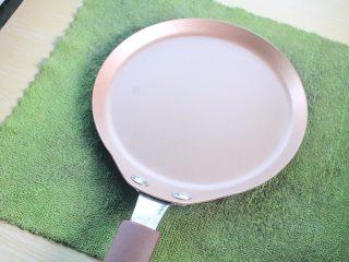那一抹毛巾卷的绿,再将平底锅放在湿毛巾上10秒左右