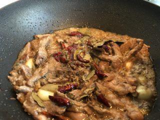 快手小食 网红五香冷吃牛,炒至牛肉全部变色后,倒入五种香料,转小火继续炒。