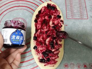 蓝莓酱玫瑰花面包#一次揉面&一次发酵#,取适量蓝莓酱均匀摸在面片上
