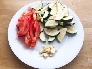 快手正餐 番茄炒西葫芦,将西红柿切成船形,西葫芦切片,大蒜拍碎备用。
