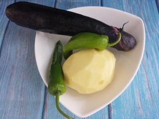 家常土豆丝炒茄丝,先洗净一根茄子,土豆洗净去皮,再洗两个小青椒。