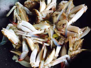 下酒菜+姜葱炒梭子蟹,把梭子蟹立着放,切口朝下,中小火慢煎2-3分钟