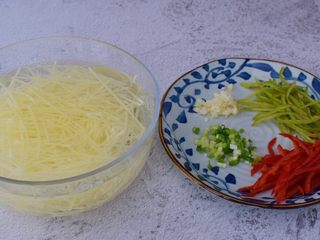 凉拌土豆丝,土豆去皮擦成丝,然后洗去淀粉再放入清水中浸泡备用,青红椒去籽洗净切成丝,蒜切末,葱切葱花