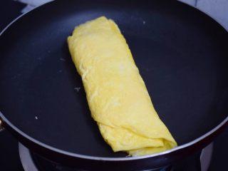 秋葵厚蛋烧,依次用同样的方法将最后1/3的蛋液卷好,再将两面煎至一会使蛋卷定型,取出晾温后再切块食用