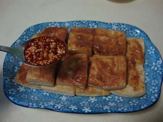 香煎豆腐,豆腐上刷层芝麻酱,把炒好的麻辣料汁浇上面