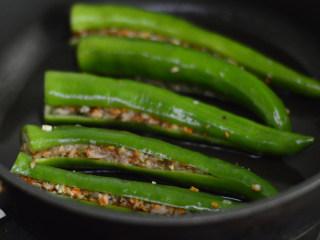 尖椒香菇酿肉,锅里倒入少许油,烧热后放入尖椒煎制