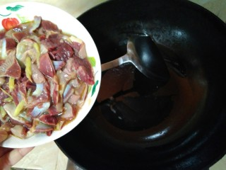 韭苔炒胗花,开火,锅中再倒入少许花生油,油热后倒入胗花中大火翻炒。
