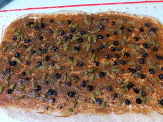 健康美味手撕包【肉桂果干黑麦面包】,在面片上均匀涂满肉桂红糖酱,均匀撒上沥干液体的水果干,底部收口处留出一部分不放馅料,并压薄底边