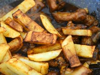 川味土豆排骨,排骨这么做非常好吃,倒入土豆条炒匀,撒少许葱花即可