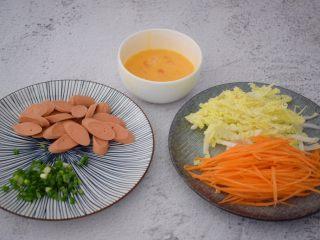 火腿肠炒面,鸡蛋打散备用,火腿肠切片,白菜洗净切丝,胡萝卜去皮洗净切丝,葱切葱花