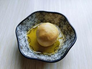 黄金南瓜芝麻球,首先将面团搓成长条,再用刀切出大小等份的小面团,取一小块面团,包上豆沙馅揉圆,再放入融化的黄油碗中。(裹上黄油1、这样是为了更容易的沾满芝麻,2、特别香)