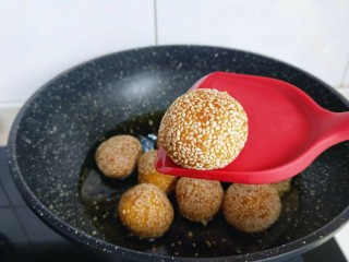 黄金南瓜芝麻球,锅中加入油, 油温5成时,依次放入南瓜麻球,转小火慢炸,翻动。