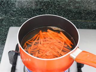 素菜培根卷,烧开适量水,倒入胡萝卜丝