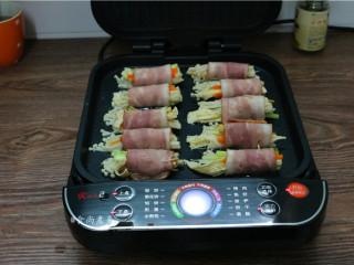 素菜培根卷,电饼铛通电烧热,烤盆内倒入食用油,将培根卷整齐铺在上面