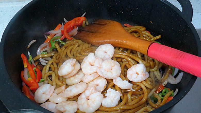 好方法成就好味道【酱炒杂蔬乌冬面】,将乌冬面从冰箱取出倒进锅中,把虾仁也倒入