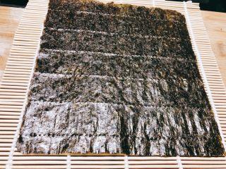 火腿肉松寿司,铺上海苔,海苔下端对准竹排下方,否则不好包。