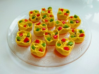 新文美食  彩色四喜蒸饺,青椒切丁,红椒切丁,摆放在花饺口中。