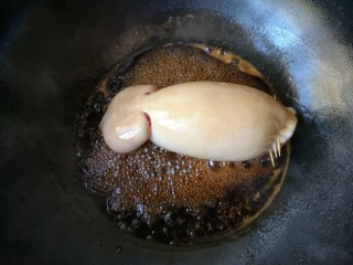 照烧鱿鱼包饭,转小火放入塞好米饭的鱿鱼,让鱿鱼均匀沾满照烧汁。