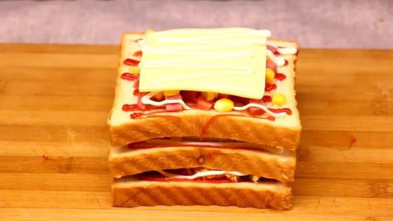 芝士三明治,第三层挤番茄沙司5克、放玉米粒20克均匀铺在上面、把台湾香肠切成丁放15克、最后把<a style='color:red;display:inline-block;' href='/shicai/ 62159'>芝士片</a>放上挤沙拉酱5克。