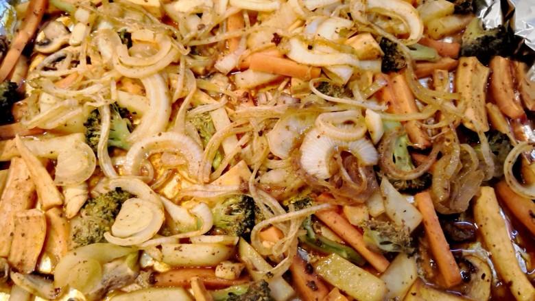 无敌烤羊腿,把烤制了40分钟的羊腿从锡纸中取出,洋葱抓出来跟混合蔬菜放到一起。