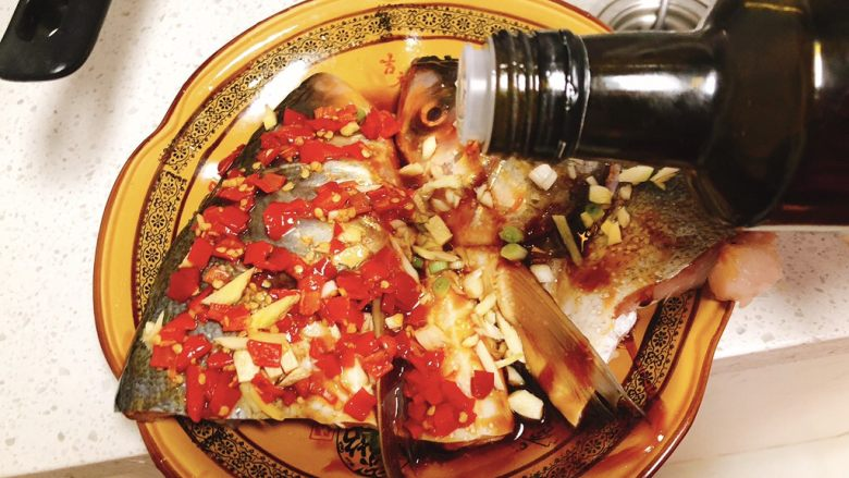 剁椒鱼头,倒入3勺茶籽油(茶籽油蒸鱼更香,没有的话食用油也可)。