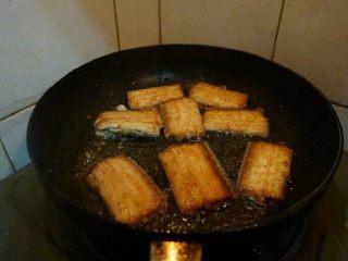 红烧带鱼,煎好一面翻面,将另一面也煎至金黄色