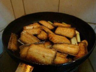 红烧带鱼,放入煎好的带鱼、料酒、盐,盖上锅盖。开中火炖5分钟左右