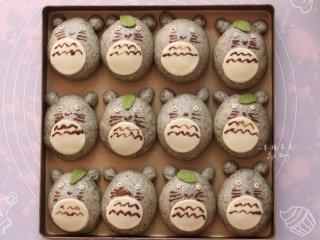 可爱的龙猫面包,面团二发结束后,将欧克皮制作的龙猫眼睛和白肚皮沾少许水轻轻贴在龙猫面团上,绿色欧克皮绿叶可以挑选点缀,最后用可可液画出龙猫的表情和花纹,眼睛也点缀一下