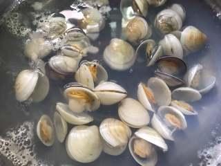 梭子蟹海鲜面,锅中倒入适量水,煮开后放入老姜片,倒入适量料酒后把清洗干净的文蛤放入锅中。