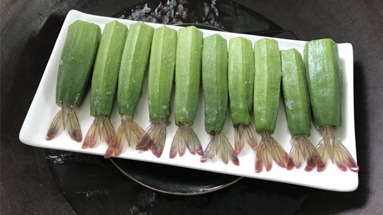 秋葵酿虾,全部做好后,将虾尾插入秋葵中。上蒸锅,水开后蒸8分钟即可。