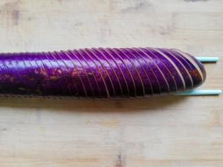 鱼香茄龙煲,茄子洗净,放在两根筷子中间,45度斜切成5mm的片,底部不切断