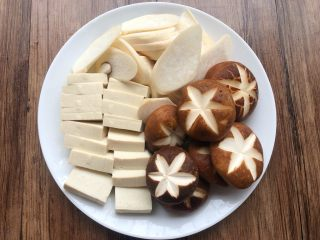 韩式泡菜锅,杏鲍菇洗净切片,香菇洗净切上花刀,豆腐冲洗一下切块