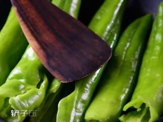 虎皮尖椒的家常做法,一学就会, 热锅冷油,放入尖椒,铲子压着煎,煎至两面起皱出现焦糊点。