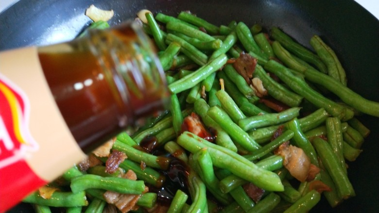 新文美食  五花肉耗油豆角焖面,倒入适量耗油。
