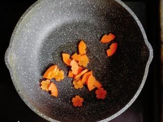 宝宝辅食—胡萝卜茼蒿鸡蛋面,锅内倒入适量的油,倒入胡萝卜翻炒至断生
