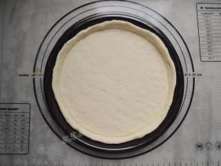 香菇培根披萨,披萨盘刷一层薄油,将圆形面饼放入披萨盘中,用手压薄底部,使中间薄边缘厚。
