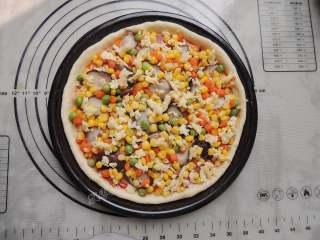 香菇培根披萨,将香菇和什锦杂蔬粒铺在饼底上,铺完蔬菜,再撒一层芝士。
