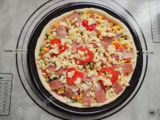 香菇培根披萨,最后将培根和红椒圈铺在最上层,再撒一些芝士。