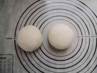 香菇培根披萨,将发酵好的面团倒出,分割成两等分,分别揉圆。