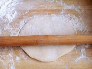 美味早餐 番茄鸡蛋牛肉手擀面,面被擀的薄了些,但是还不太理想,再撒上面粉,用擀面杖卷起面饼继续再擀。