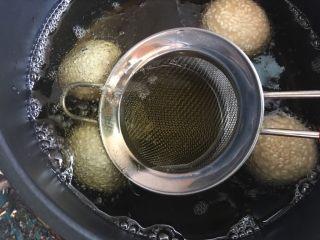 空心麻团(麻圆),用铲子或过滤筛子压下去