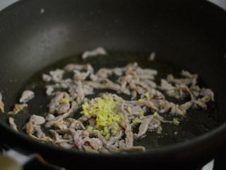 干煸菜花,炒至肉丝变色后加入姜末,翻炒均匀