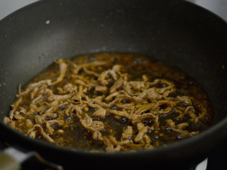 干煸菜花,调入酱油和料酒,翻炒上色