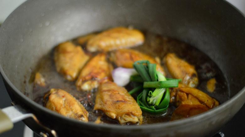 啤酒鸡翅,放入葱结,盖上盖子转小火焖煮约20分钟