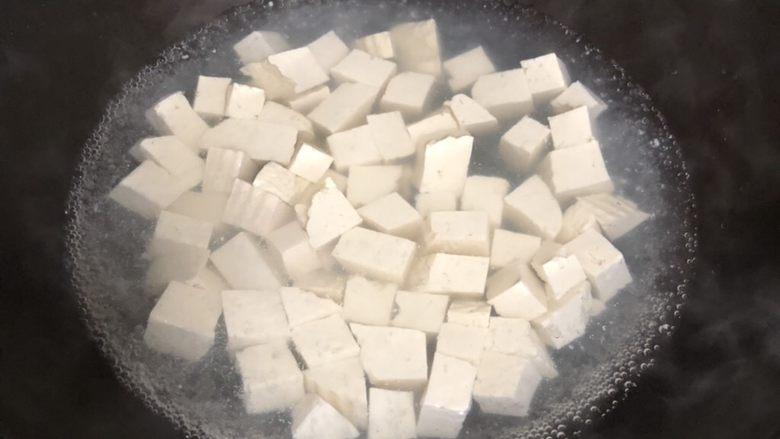 十味 家常豆瓣烧豆腐,锅中放盐(配方外)水烧开之后,将豆腐块放入锅中焯水。