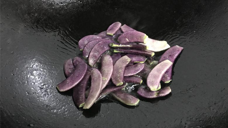 毛豆炒羊眼豆,锅中倒入适量油,先把羊眼豆放入煸炒一下。